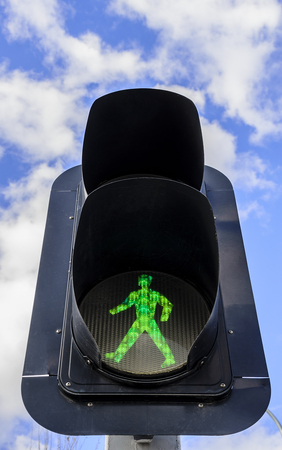 Close up view of a pedestrian crossing light under the blue sky