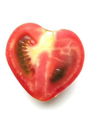 Photo of a ripe cut tomato in the shape of a heart isolated over white