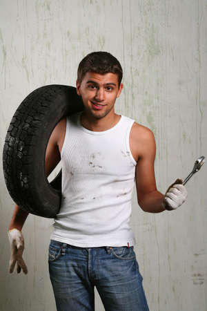 A young mechanic holding tyre and wrench