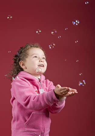 A little girl catching soap bubbles Stock Photo