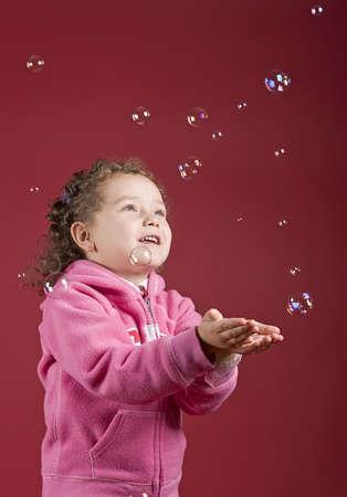 A little girl catching soap bubbles Banco de Imagens
