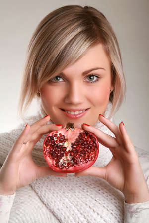 Studio shot of beautiful young adult holding pomegranate