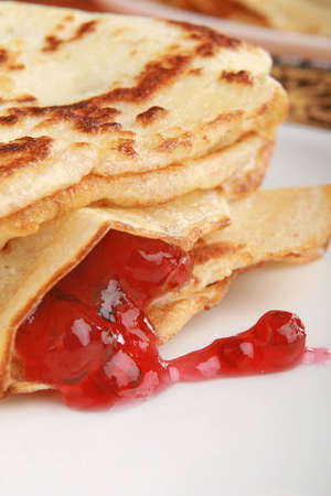 stack of pancakes filled with red jam