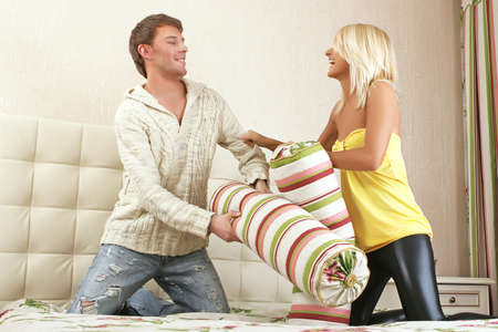 young man and woman withing with pillows on bed Foto de archivo