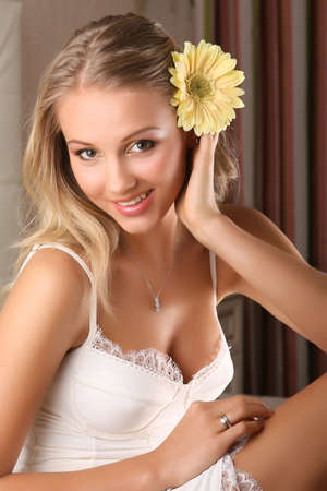 young beautiful woman holding flower and smiling to the camera