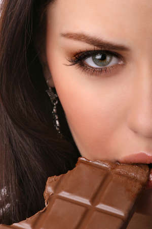 part of female face with chocolate bar Stock Photo