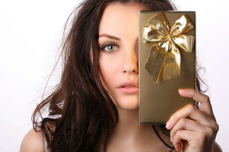 Beautiful woman covers her face with present