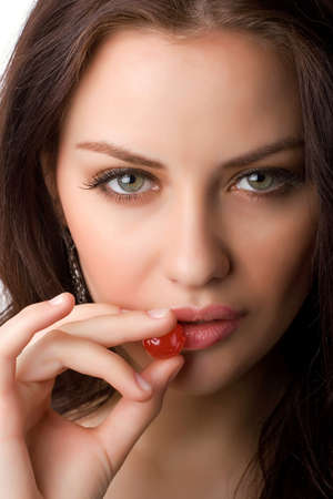 closeup portrait of attractive woman holding berry isolated on white