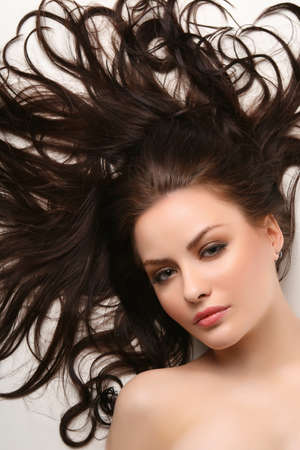 young adult lying on white background with beautiful hair all over Stock Photo