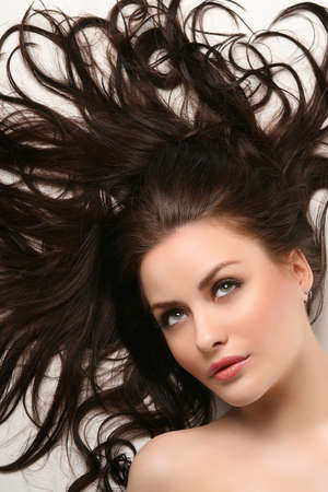 hair treatment: young adult lying on white background with beautiful hair all over Stock Photo
