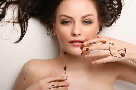 Attraktive junge Frau liegt auf weißem Hintergrund mit Schokolade verschmiert Standard-Bild - 4541869