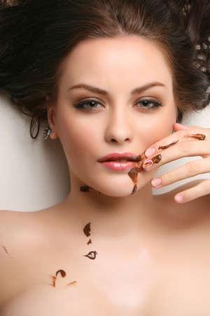 Attraktive junge Frau liegt auf weißem Hintergrund mit Schokolade verschmiert Standard-Bild - 4541833