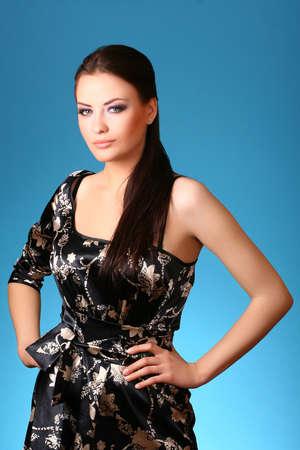 aantrekkelijke jonge vrouw op blauw  Stockfoto