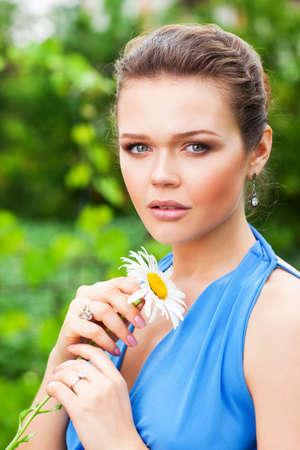 portret van aantrekkelijke glamoureuze vrouw in bloemen tuin bedrijf  Stockfoto