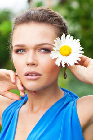 attractive young lady holding chamomile and looking away photo