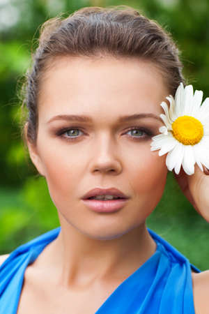closeup portrait of attractive caucasian woman holding chamomile near her face and looking at camera photo
