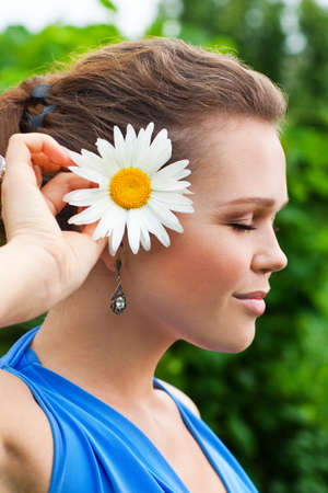 profile of attractive young adult with camomile on fresh air Stock Photo - 7586170