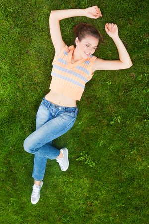 attractive caucasian girl lying down on her back at the green lawn and laugh out loudly photo
