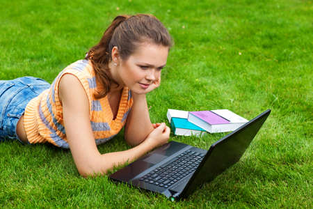 pretty young adult with laptop lying on green grass photo