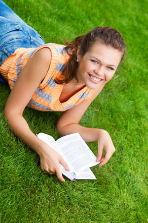 pretty teenager reading a book on the grass photo