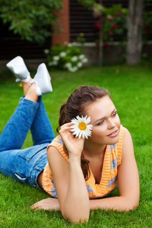 attractive young teenager with flower lying on green grass photo