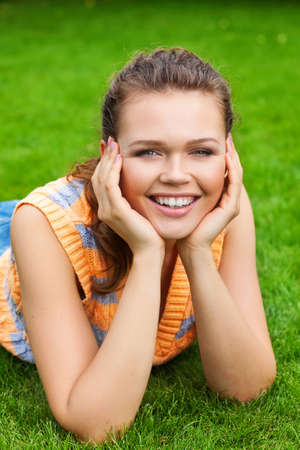 pretty young adult lying on lawn and laugh to the camera Stock Photo - 7586249