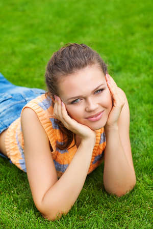 attractive caucasian girl on green lawn looking at camera photo