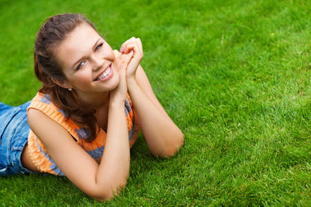 attractive teenager lying on green lawn smile to the camera photo