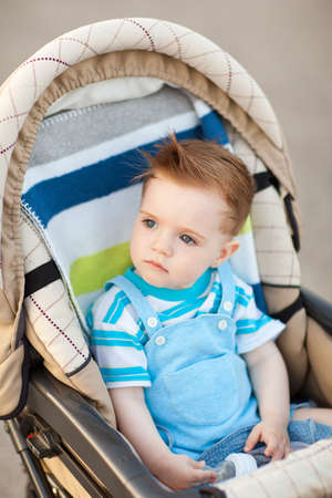looking away from camera: beautiful caucasian 1 year old baby sitting in carriage and looking away from camera
