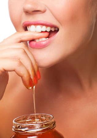 Close-up van vrouwelijke mond met mooie glimlach eten van honing met handen geïsoleerd op witte achtergrond