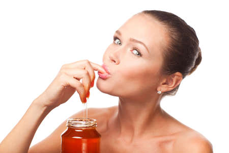 attractive young adult with honey holding finger in the mouth isolated on white background Stock Photo