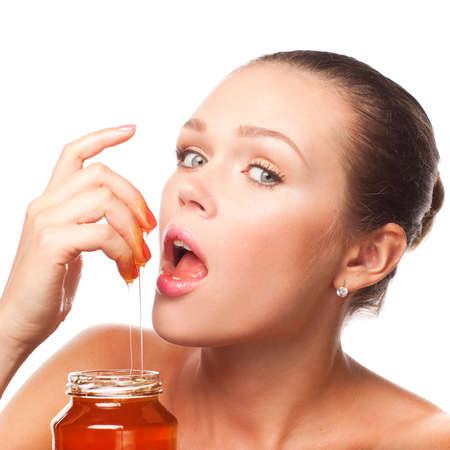 aantrekkelijke jonge volwassene met honing in de pot geïsoleerd op wit Stockfoto