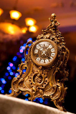 old antique clock with angel figurines over Christmas tree bokeh background
