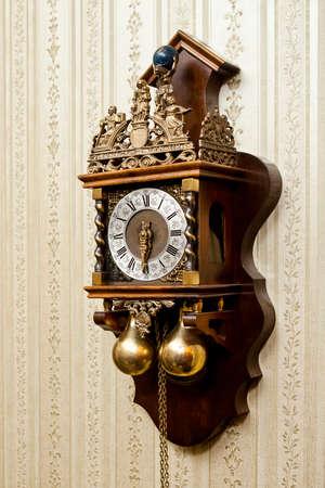 orologi antichi: vecchio orologio in legno antico con sculture per metallo appesa al muro