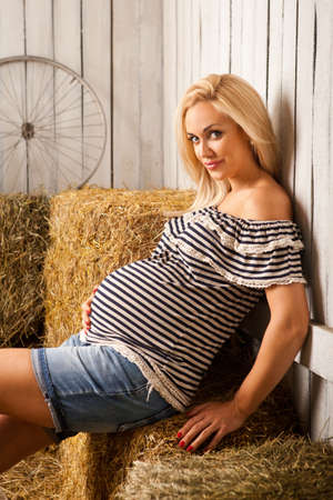 beautiful pregnant blonde woman sitting on hay caressing her belly Stock Photo