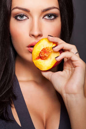 Portret van jonge mooie sexy vrouw met sappige perzik in haar hand