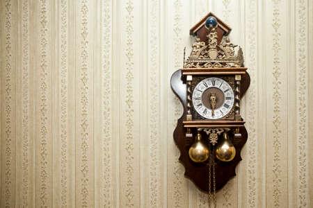 antique clock: viejo reloj antiguo de madera con tallas de metal que cuelga en la pared