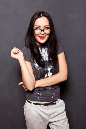 smiling beautiful woman in stylish glasses on grey background