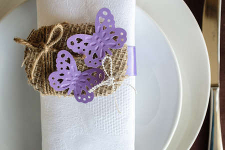 butterfly knife: napkin decorated with two violet butterflies and twine tied in a bow