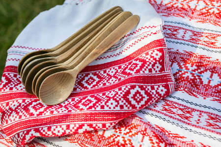 folk village: Wooden spoons on table cloth embroidered with red and white folk ornament