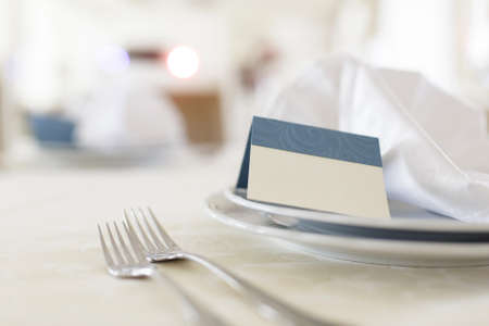 serviette: wedding table appointments. closeup forks and plates with invitation Stock Photo