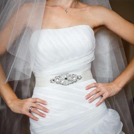 mani sui fianchi: sposa in abito di lusso decorato con le braccia sui fianchi