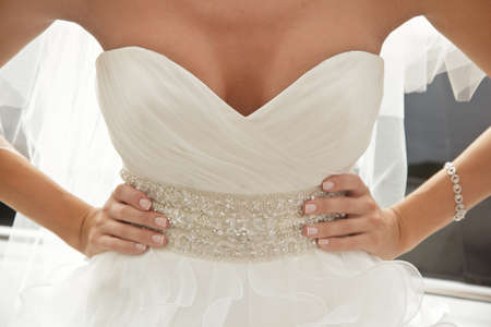 bride in luxury dress with plunging neckline, arms akimbo Stockfoto