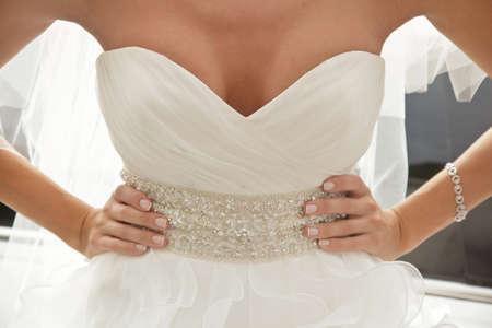 bruid in luxe jurk met decollete, armen over elkaar Stockfoto