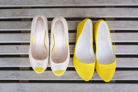 open toe: yellow ballet shoes and high heels open toe shoes on wood boards Stock Photo