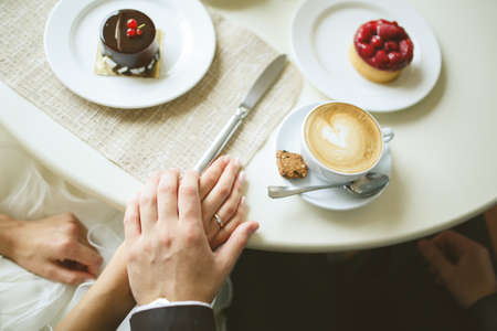 hands of bride and groom on table with cakes and cup of cappuccino photo