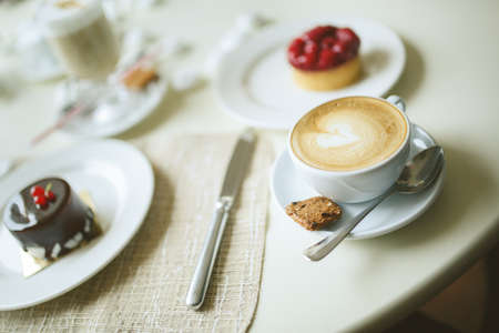 cup of cappuccino and delicious cakes with chocolate and strawberry and  on table