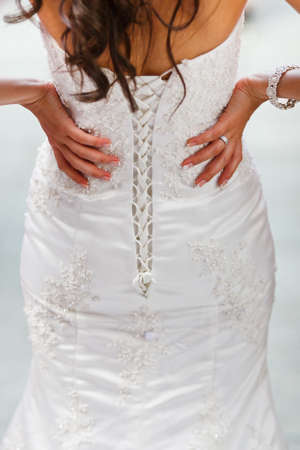 arms akimbo: closeup of white wedding dress back Stock Photo