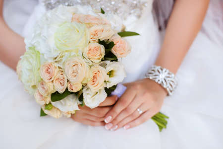 bride bangle: beautiful wedding bouquet of roses and eustoma flowers in hands of the bride