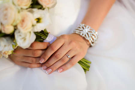 bride bangle: beautiful wedding bouquet of roses and eustoma flowers in hands of the bride, french manicure